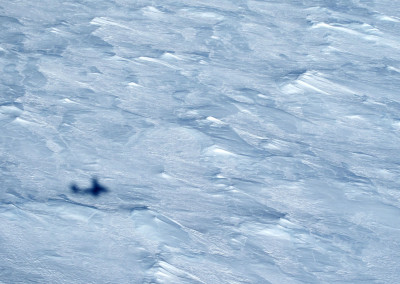 Rough ice surface with aircraft shadow.